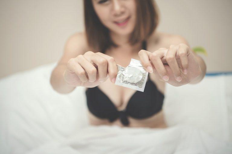 Mulher na cama com preservativo masculino em mãos